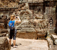 Tourist photographing bas-reliefs in temple. Angkor, Cambodia Royalty Free Stock Image
