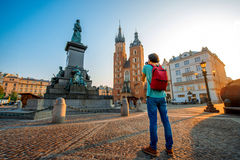 Tourist photographing in the center of Krakow. Male tourist with backpack photographing famous Polish basilica in the center of Krakow Stock Photo