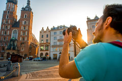 Tourist photographing in the center of Krakow. Male tourist with backpack photographing famous Polish basilica in the center of Krakow Stock Images