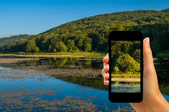 Tourist photographing Cesarò lake with smartphone Stock Images