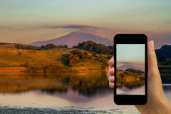 Tourist photographing Cesarò lake and volcano Etna with smartphone Royalty Free Stock Image