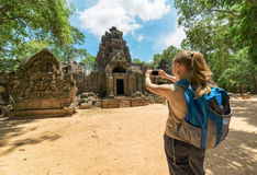 Tourist photographing the entrance to temple in Angkor, Cambodia Royalty Free Stock Images