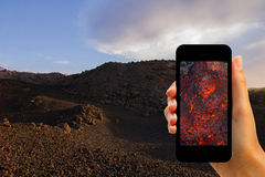 Tourist photographing eruption on Volcano Etna with smartphone Stock Image