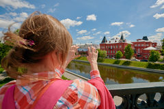 Tourist photographing on excursion. Back view of woman photographing famous palace during excursion. Russia, Orel city orlik embankment state bank building Stock Image