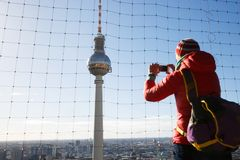 Tourist photographing the TV Tower, Fernsehturm in Berlin stock image