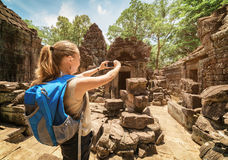 Tourist photographing old pavilion of temple in Angkor, Cambodia Royalty Free Stock Image
