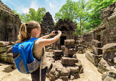 Tourist photographing pavilion of ancient temple in Angkor, Camb Stock Images
