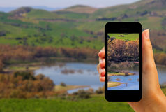 Tourist photographing Pozzillo lake and volcano Etna with smartphone Stock Images