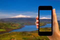 Tourist photographing Pozzillo lake and volcano Etna with smartphone Stock Image