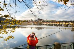 Tourist photographing Prague with Charles Bridge and Hradcany. Tourist taking picture of autumn Prague cityscape with Charles Bridge across Vltava and the royalty free stock photo
