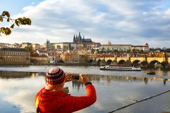 Tourist photographing Prague with Charles Bridge and Hradcany. Tourist admiring autumn cityscape of Prague city with Charles Bridge across Vltava and the royalty free stock image