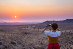 Tourist photographing with smartphone the stunning view of barren valley in the Namib desert, majestic visitor attraction in Namib Stock Images