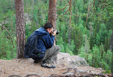 Tourist photographing on the top of taiga forest. Stock Images