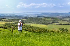 Tourist photographing tuscan landscape Stock Images