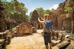 Tourist photographing unique bas-relief in Angkor, Cambodia Stock Photos