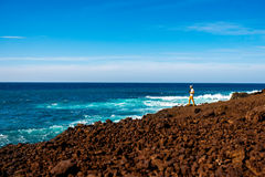 Tourist photographing volcanic coast on Lanzarote island in Spain Royalty Free Stock Photos