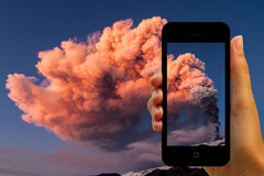 Tourist photographing the volcano eruption on smartphones Royalty Free Stock Image