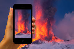 Tourist photographing the volcano eruption on smartphones Stock Images