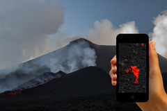 Tourist photographing the volcano eruption on smartphones Royalty Free Stock Images