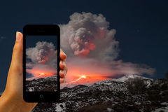 Tourist photographing the volcano eruption on smartphones Stock Photo