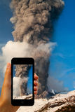 Tourist photographing the volcano eruption on smartphones Stock Image