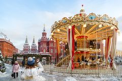Tourist photographs a carousel at the Manege Square during the New Year holidays. MOSCOW, RUSSIA, FEBRUARY 01, 2018: Tourist photographs a carousel at the Manege Royalty Free Stock Photography