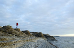 A tourist photographs at coast by stone formations. In the island Oland in Sweden Stock Images