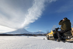 Tourist photographs eruption volcano sitting on a snowmobile Royalty Free Stock Photo