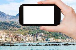 Tourist photographs Giardini-Naxos town in Sicily. Travel concept - tourist photographs Giardini-Naxos town in Sicily Italy in summer season on smartphone with Royalty Free Stock Photos