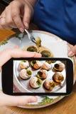 Tourist photographs hot plate of escargot shells Royalty Free Stock Image