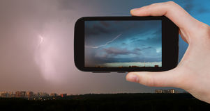 Tourist photographs of lightning bolt over city Royalty Free Stock Photography