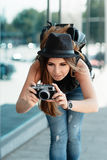 Tourist photographs with mirrorless digital camera. The beautiful calm girl student in a stylish casual hat photographs something with small digital camera Royalty Free Stock Photo