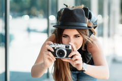 Tourist photographs with mirrorless digital camera. The beautiful calm girl student in a stylish casual hat photographs something with small digital camera Stock Image