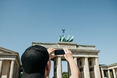 Tourist photographs on a mobile phone the Brandenburg Gate in Berlin in Germany. Sightseeing royalty free stock image