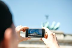 Tourist photographs on a mobile phone the Brandenburg Gate in Berlin in Germany. Sightseeing stock image