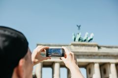 Tourist photographs on a mobile phone the Brandenburg Gate in Berlin in Germany. Sightseeing stock photos