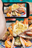 Tourist photographs of plate with crab and seafood Royalty Free Stock Image