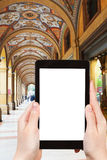 Tourist photographs of portico in Bologna, Italy. Travel concept - tourist photograph medieval artistic portico on piazza Cavour in Bologna, Italy on tablet pc Royalty Free Stock Photo