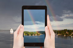 Tourist photographs of rainbow over Baltic sea Stock Images