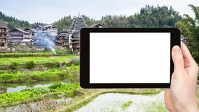 Tourist photographs rice fields in Chengyang. Travel concept - tourist photographs rice fields near irrigation canal in Chengyang village of Sanjiang Dong Stock Images