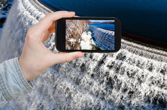 Tourist photographs of river waterfall on dam Royalty Free Stock Photo