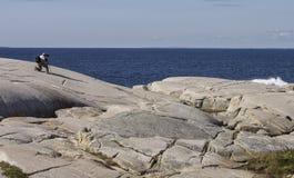 Tourist photographs the rocky coast of Peggy's Cove Nova Scotia September 2014. Royalty Free Stock Photography