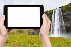 Tourist photographs Seljalandsfoss waterfall. Travel concept - tourist photographs Seljalandsfoss waterfall of Seljalands River  in autumn on tablet with cut out Royalty Free Stock Photo