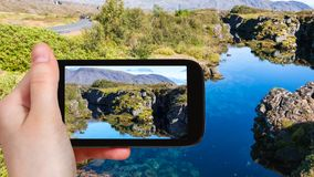 Tourist photographs Silfra fissure in rift valley. Travel concept - tourist photographs Silfra fissure in rift valley of Thingvellir national park in Iceland in Stock Photography