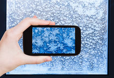 Tourist photographs snowflakes and frost on window Royalty Free Stock Photography