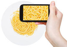 Tourist photographs of spaghetti al burro on plate Royalty Free Stock Image