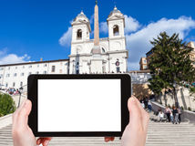 Tourist photographs Spanish Steps in Rome city. Travel concept - tourist photographs Church Santissima Trinita dei Monti and Spanish Steps in Rome city on tablet Royalty Free Stock Photography