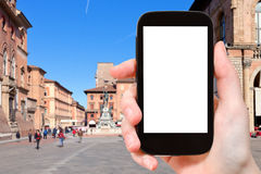 Tourist photographs square in Bologna city. Travel concept - tourist photographs square in Bologna city on smartphone with cut out screen with blank place for royalty free stock images