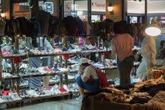 Tourist picking a shoe at asiatique. Tourist picking a shoe and bag at night market - asiatique bangkok thailand Royalty Free Stock Photos