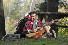 Tourist Playing Guitar in the Woods Stock Image